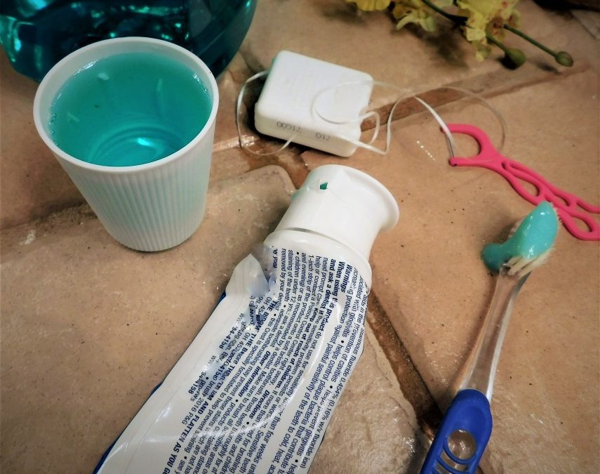 A cup of mouthwash, tube of tooth paste and container of floss sitting on a bathroom