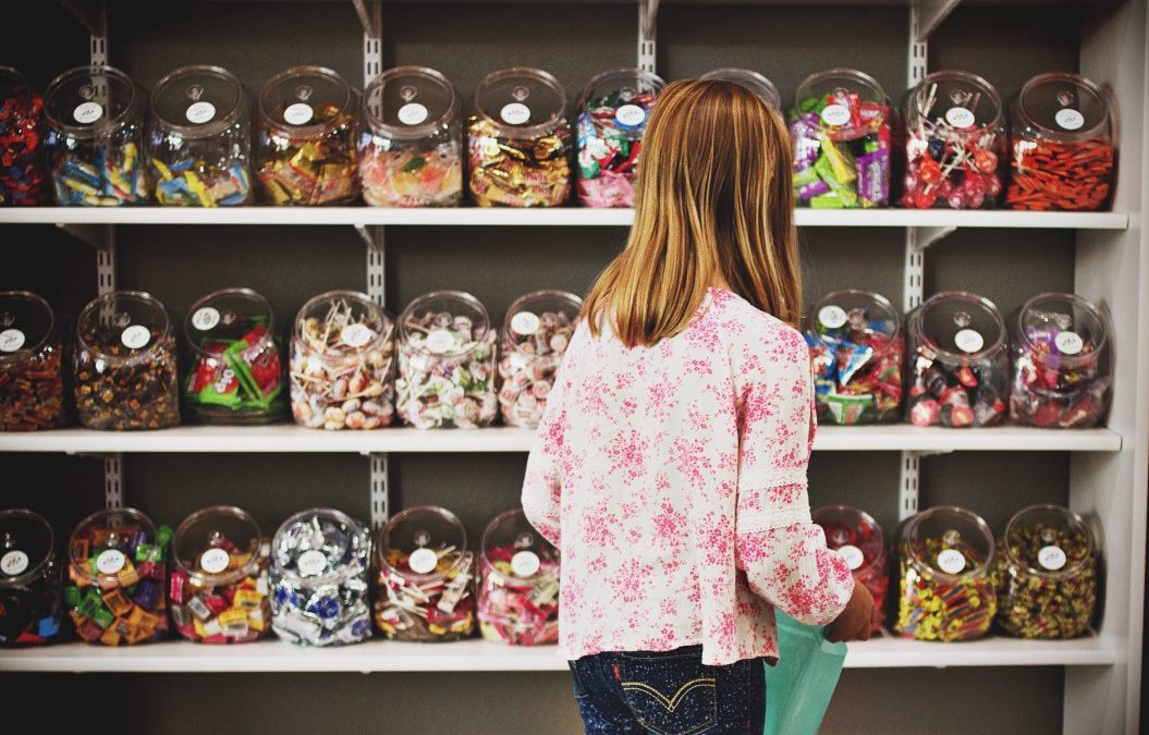 child looking at a wall of candy in a candy shop
